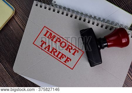 Red Handle Rubber Stamper And Import Tariff Text Isolated On The Table.