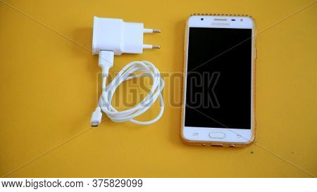 Salvador, Bahia / Brazil - July 10, 2020: Charger Is Seen Next To Cell Phone Is Seen In The City Of