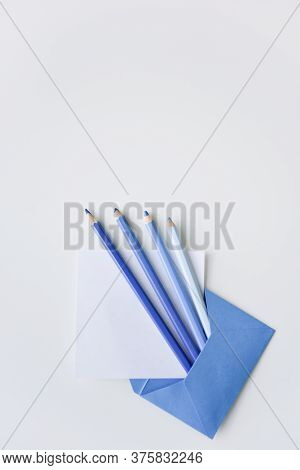 Selective Focus, Four Blue Pencils And White Paper Sheet Out Of The Blue Envelope