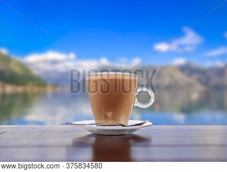 Cup Of Hot Latte Coffee With The Blurred View Of Kotor Bay Or Boka Kotorska In The Background In The