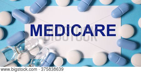 The Inscription On A White Sticker On A Blue Background Near White And Blue Pills. Text: Medicare, M