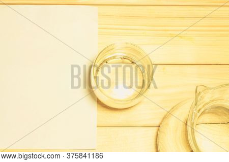 Close Up Shot Of A  Glass Of Water And A Pitcher Next To An Empty White Plain Piece Of Paper On A Wo