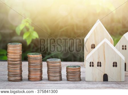 Wood House Model With Stack Of Coins On Wooden Table With Green Nature Blur Background And Sunray. S