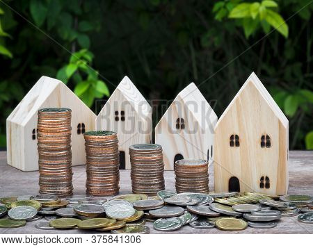Wood House Model With Stack Of Coins On Wooden Table With Green Nature Blur Background. Savings Plan