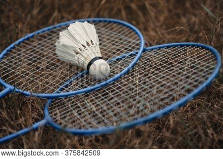 Metal Badminton Rackets And A White Feather Shuttlecock. The Game Of Badminton. Hobbies And Outdoor