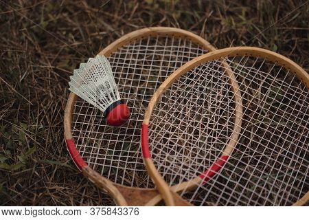 Wooden Badminton Rackets And A White Plastic Shuttlecock With A Red Head. The Game Of Badminton. Hob