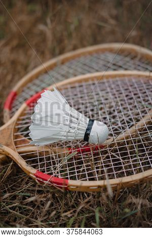 Wooden Badminton Rackets And A White Feather Shuttlecock. The Game Of Badminton.
