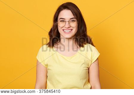 Smiling Happy Woman Wearing Yellow Casual T Shirt And Eyewear Looking Directly At Camera With Happy