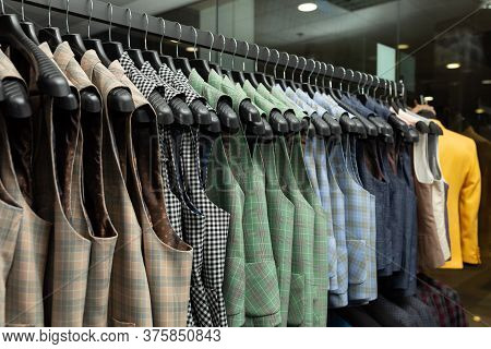 Stylish Male Vests On Hangers In The Row. A Lot Of Beatiful Vests In A Row