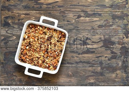 Granola With Honey And Nuts In A Baking Dish On A Wooden Background.