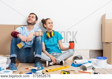 Happy Smiling Couple Relaxing On Floor With Cup Of Coffee Among Construction Tools And Materials. Ho