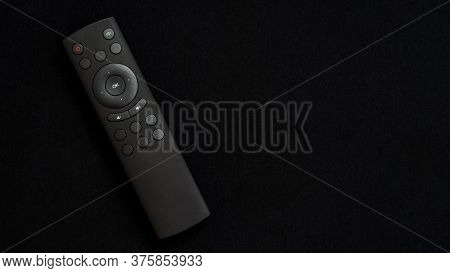 Black Television Remote Control On A Black Embossed Background. Tv Control And Program Switching. Sm
