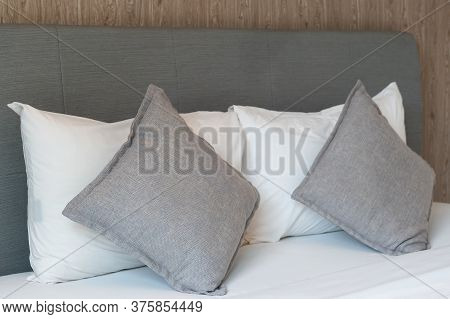 Luxury Stacking Of Pillows On Bed, White Bed Sheets With Wooden Bedhead.