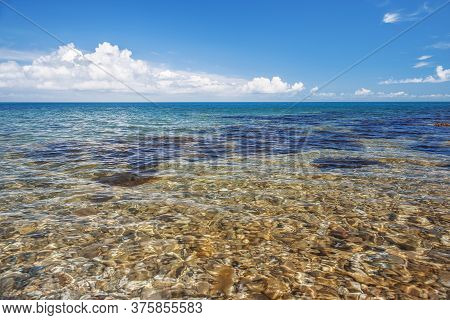 Sea With A Rocky Bottom And Large Clouds On The Horizon. Clear And Clear Water. Blue Sky With Large