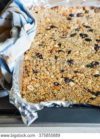Home Made Energy Granola With Nuts, Dried Fruit, Peanut Butter And Superfoods Baked In Baking Tin To