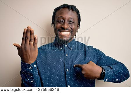 Young african american man showing golden marriage ring on finger over white background with surprise face pointing finger to himself