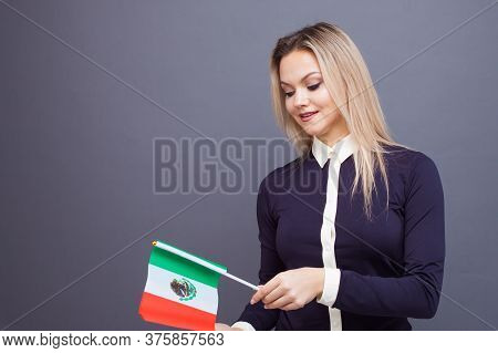 Immigration And The Study Of Foreign Languages, Concept. A Young Smiling Woman With A Mexico Flag In