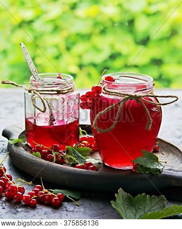 Red Currant Jam In Curly Glass Jars On A Black Concrete Background. Jam Recipes. Harvest Berries. Se