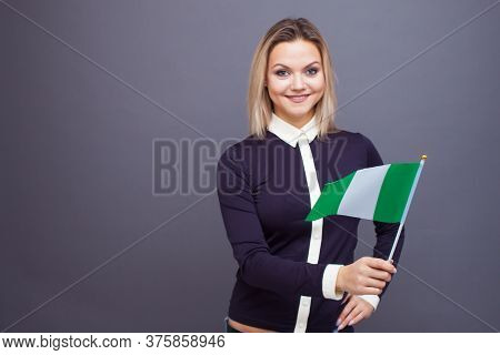 Immigration And The Study Of Foreign Languages, Concept. A Young Smiling Woman With A Nigeria Flag I