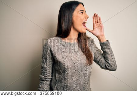 Young beautiful brunette woman wearing casual sweater over isolated white background shouting and screaming loud to side with hand on mouth. Communication concept.