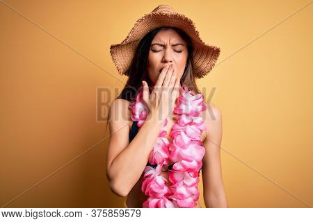 Young beautiful woman with blue eyes on vacation wearing bikini and hawaiian lei bored yawning tired covering mouth with hand. Restless and sleepiness.