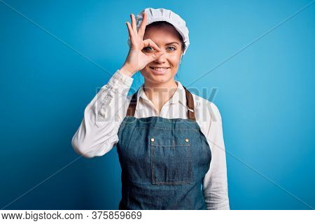 Young beautiful baker woman with blue eyes wearing apron and cap over blue background doing ok gesture with hand smiling, eye looking through fingers with happy face.