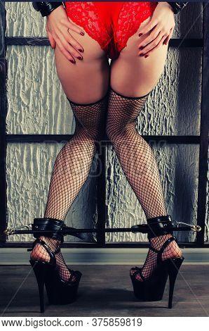 Bdsm Outfit For Adult Sex Games. Women's Legs In Black Stockings In A Mesh In High Heels Are Shackle