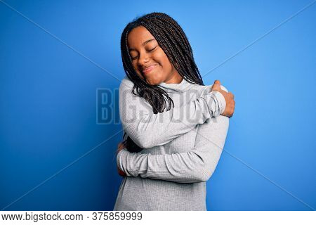 Young african american woman standing wearing casual turtleneck over blue isolated background Hugging oneself happy and positive, smiling confident. Self love and self care