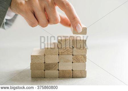 Women Hand Putting A Wooden Block On Top And Arranging Wooden Blocks Stacking, Business Concept For