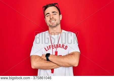 Handsome lifeguard man wearing t-shirt with red cross and whistle over isolated background happy face smiling with crossed arms looking at the camera. Positive person.