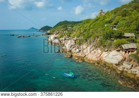 Tropical island coastline, Coast of Koh Tao island with turquoise clear water, boat and people snorkeling, bungalows with sea view, sunny day. Famous destination for travel holidays in Thailand