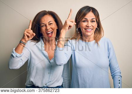 Middle age beautiful couple of sisters standing over isolated white background pointing finger up with successful idea. Exited and happy. Number one.