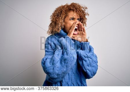 Young beautiful african american woman wearing turtleneck sweater over white background Shouting angry out loud with hands over mouth