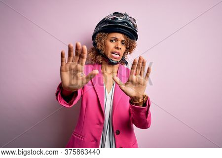 African american motorcyclist woman with curly hair wearing moto helmet over pink background afraid and terrified with fear expression stop gesture with hands, shouting in shock. Panic concept.