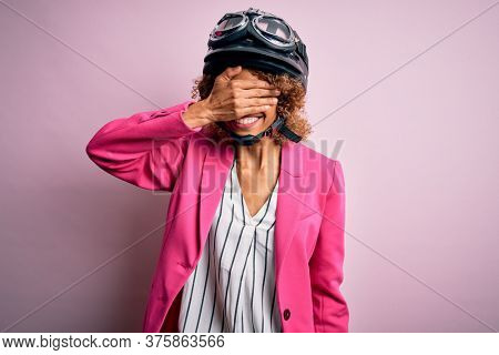 African american motorcyclist woman with curly hair wearing moto helmet over pink background smiling and laughing with hand on face covering eyes for surprise. Blind concept.