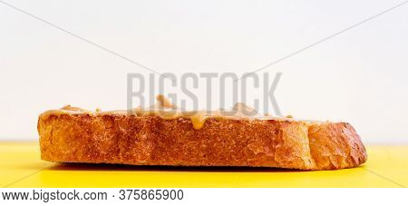 Peanut Paste Butter Sandwich On Toasted Bread On Yellow Background. Close-up. Copy Space For Your Te