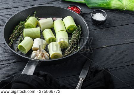 Raw Braised Leek Sultan On Grill Pan Uncooked With Herbs Ingredients  , On  Black Wooden Table Side