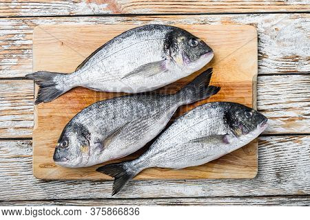 Raw Dorada Or Sea Bream On Choppong Board Over White Wood Table Top View.