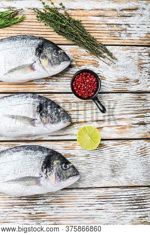 Whole Dorado Sea Bream Fish With Herbs For Grill Over White Wood Table Top View Space For Text.