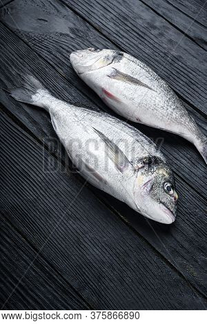 Raw Whole Pair  Dorado Or Sea Bream Fish Ob Black Wooden Table Side View.