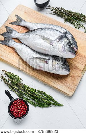 Dorado Or Seabream Fish Set On Chopping Board With Herbs For Grill Uncooked  On White Textured Backg