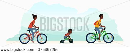 A Young Family With Child Rides Bicycles. Mom, Dad And Their Son Ride Bikes On Nature. African Ameri