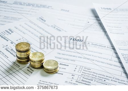 1040 Us Tax Form With Golden Coins. Taxation Concept