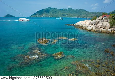 Koh Tao, Thailand - February 7, 2020: Tropical vacation. Lomprayah High Speed Catamaran arriving to popular destination. Turquoise clear water, rocky bottom, house with red roof behind boulders.