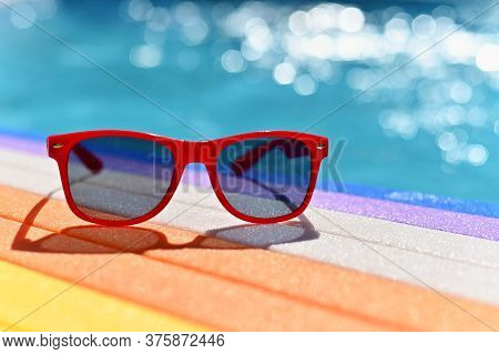 Summer Background. Concept For Summer And Vacation. Red Sunglasses By The Pool In The Background Wit