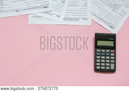 Us Tax Form 1040 With Calculator. Tax Form. Law Document Usa. Pink Background. Mathematics Business