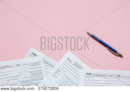 Us Tax Form 1040 With Pen. Tax Form. Law Document Usa. Pink Background. Mathematics Business Concept