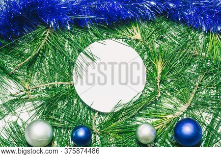 X-mas Background With Blue Decoration, Christmas Balls And Green Pine Leaves. Round Copy Space For T