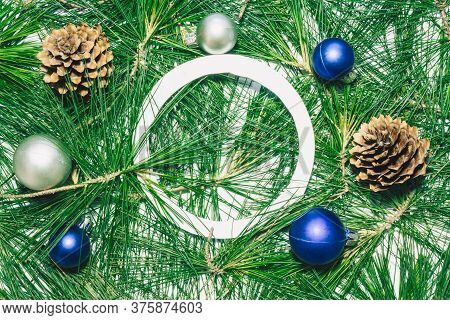 X-mas Background With Christmas Balls, Pinecones And Green Pine Leaves. Empty Circle Copy Space For