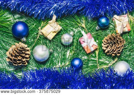 X-mas Background With Blue Decoration, Christmas Balls, Presents, Pinecones And Green Pine Leaves.